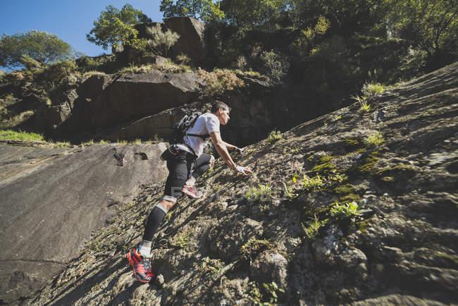 Ультра-бегун, поднимающийся по склону скалы — стоковое фото