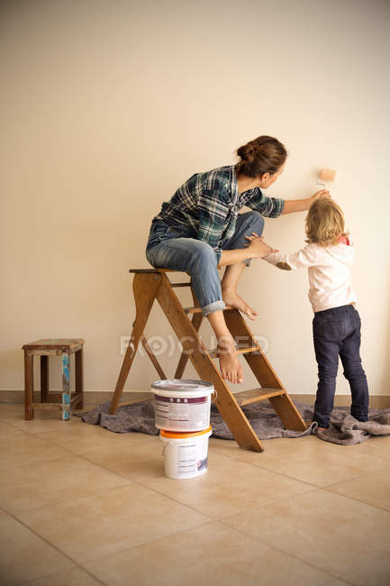Мать и дочь красят стену в новой квартире — стоковое фото