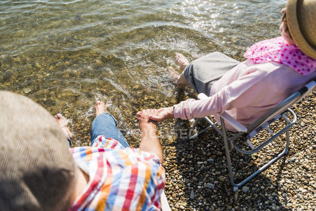 Senior couple sitting hand in hand on folding chairs at riverside — Stock Photo