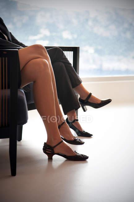 Ноги двух предпринимателей сидят siede бок на два кресла — стоковое фото
