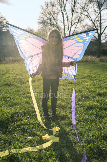 Young girl with butterfly kite on green meadow — Stock Photo