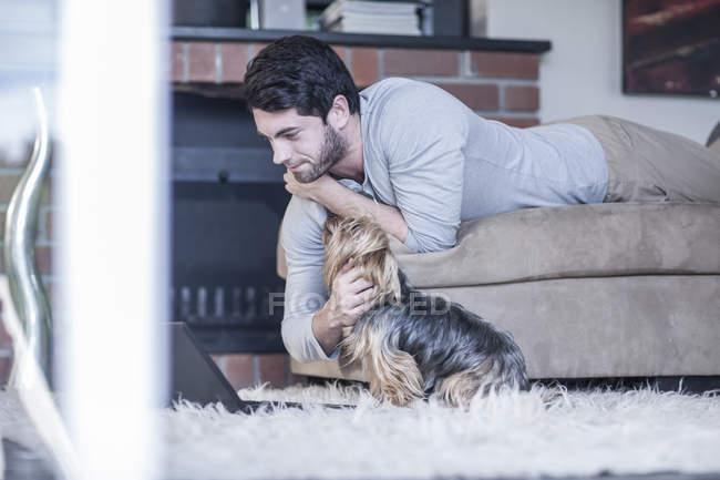 Людина з собакою, лежачи на дивані, дивиться на ноутбук — стокове фото