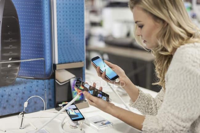 Jeune femme en comparant les deux smartphones dans un magasin — Photo de stock