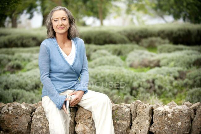 Портрет зрелой женщины, сидящей на стене в саду — стоковое фото