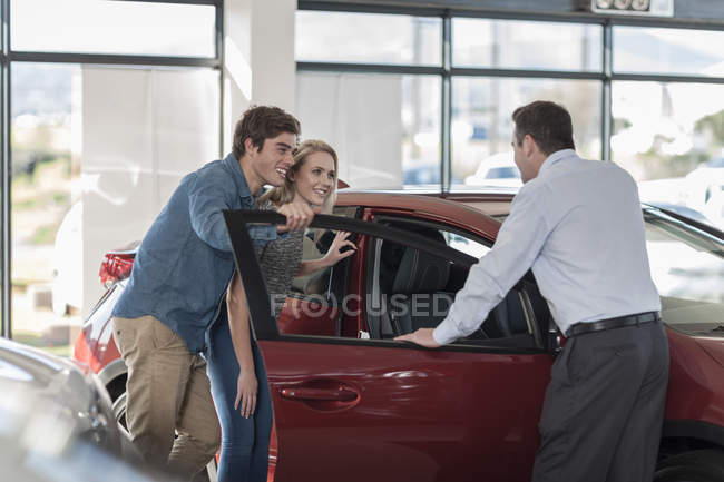Car dealer showing new car to young couple in showroom — Stock Photo