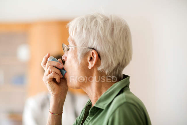White-haired senior woman using inhaler — Stock Photo
