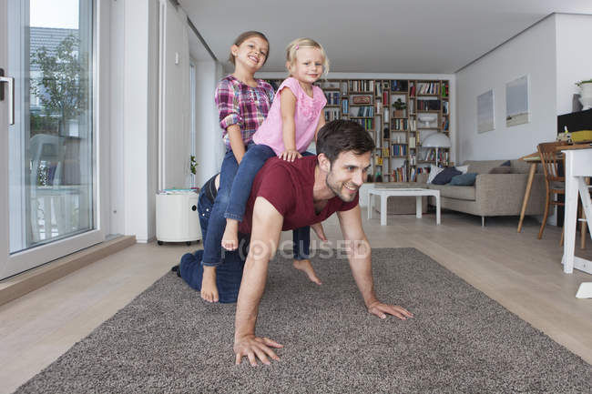 Man playing with his little daughters  in the living room — Stock Photo