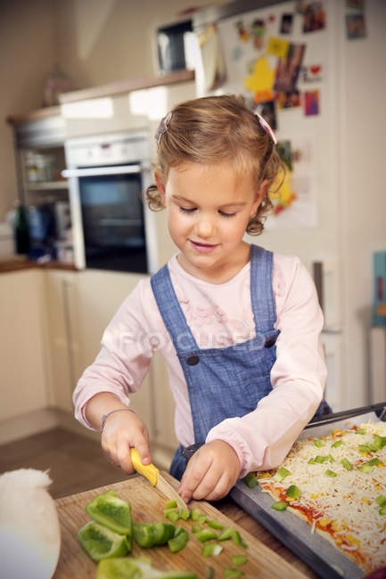 Girl cutting pepper for preparing pizza in kitchen — Stock Photo