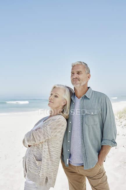 Pareja madura de pie en la playa - foto de stock