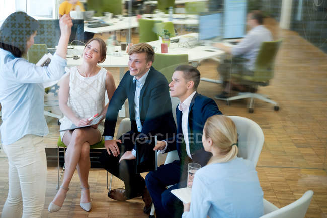 Young Businesswoman talking to expectant businessspeople in office — Stock Photo