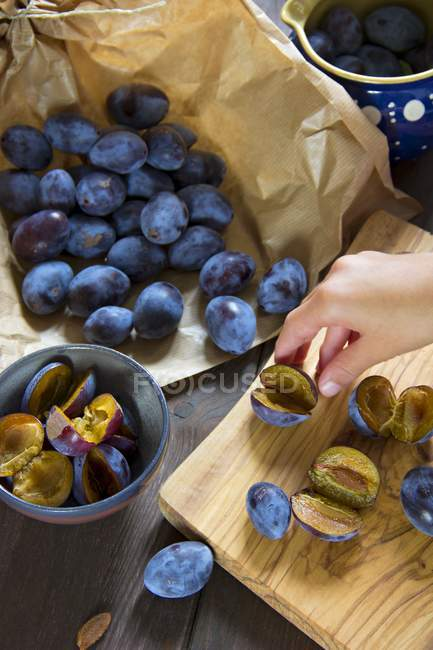 Human hand halving plums — Stock Photo