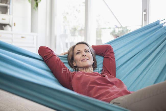 Femme souriante à la maison couchée dans l'hamac — Photo de stock