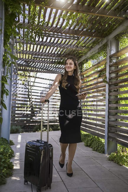 Smiling businesswoman with mini tablet and wheeled luggage — Stock Photo