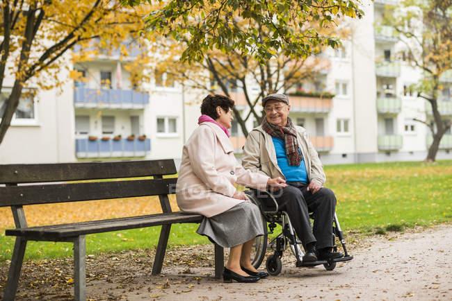 Старшая женщина сидит на скамейке рядом с мужем в инвалидном кресле — стоковое фото