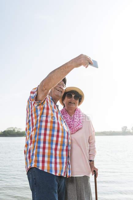 Älteres paar unter einem Selfie im riverside — Stockfoto