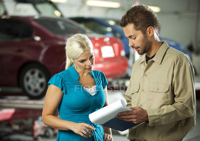 Homem e cliente discutindo a lista de verificação na garagem de reparação — Fotografia de Stock