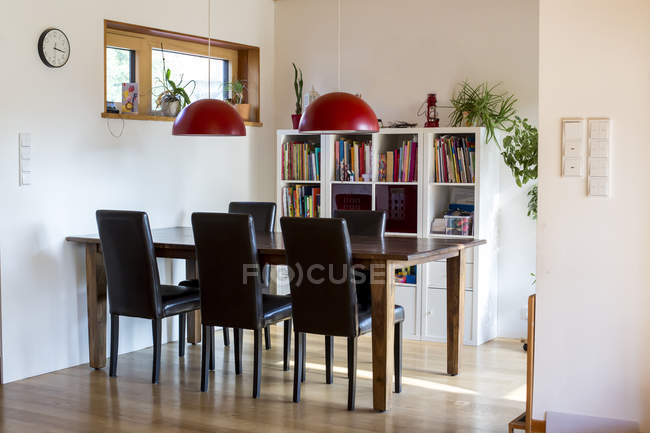 Daytime view of modern dining room with bookshelves — Stock Photo