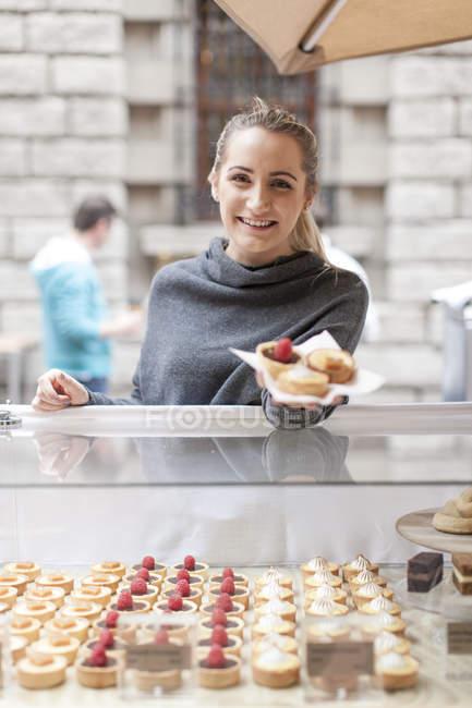 Молода жінка продає тістечка на ринку — стокове фото