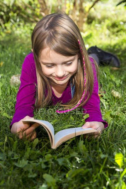 Menina feliz deitado na grama e livro de leitura — Fotografia de Stock
