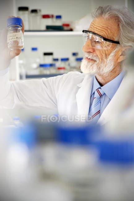 Старший професор, дивлячись на лабораторний скляний — стокове фото