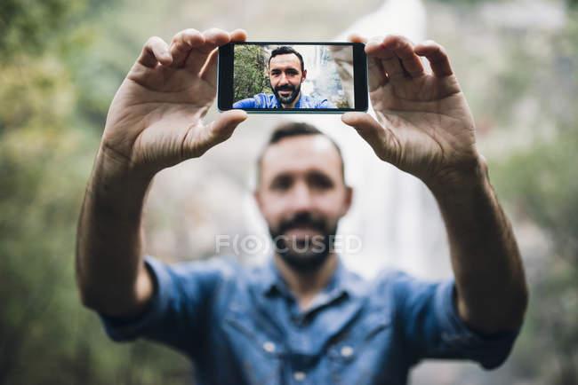 Bärtiger Mann unter einem Selfie mit Smartphone vor einem Wasserfall — Stockfoto