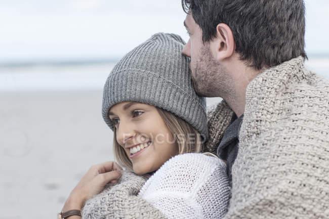 Счастливая молодая пара обнимается на пляже — стоковое фото