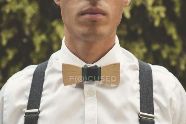 Jeune homme portant un noeud papillon en bois, gros plan — Photo de stock