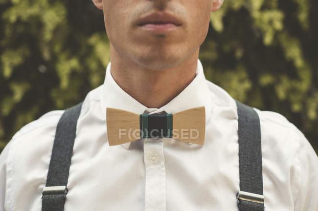 Young man wearing a wooden bow tie, close-up — Stock Photo