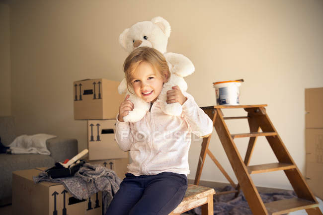 Girl sitting with teddy bear and cardboard boxes on background — Stock Photo