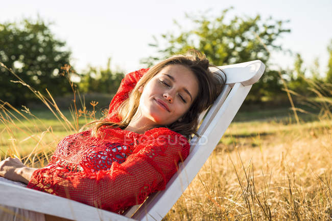 Portrait of woman relaxing on a deck chair on a meadow — Stock Photo