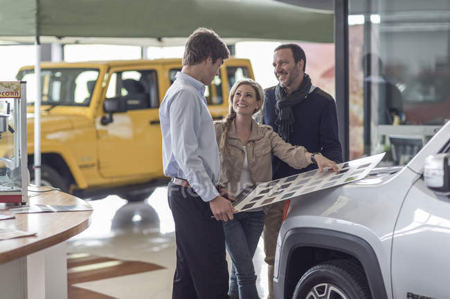 Couple choosing from color sample at car dealer — Stock Photo