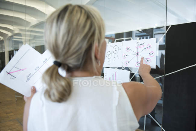 Businesswoman in office pointing at mind map — Stock Photo