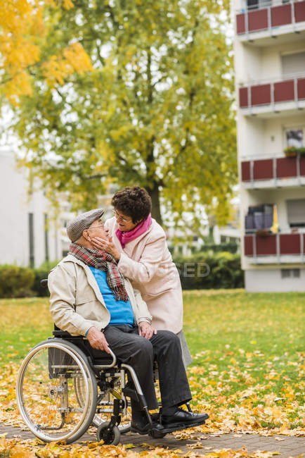 Senior woman looking at husband in wheelchair — Stock Photo