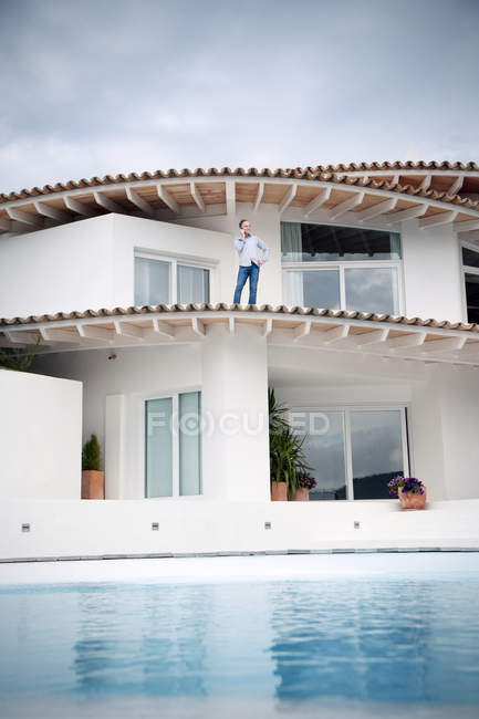 Spain, Mallorca, man standing on roof of his house telephoning — Stock Photo