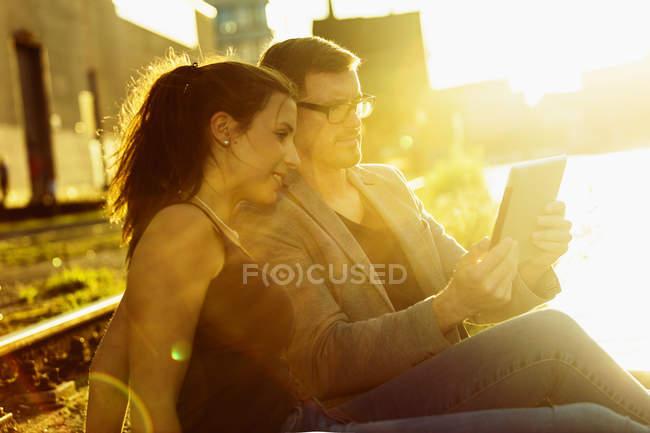 Pareja con tableta digital relajarse en el puerto de la ciudad en el crepúsculo de la noche - foto de stock