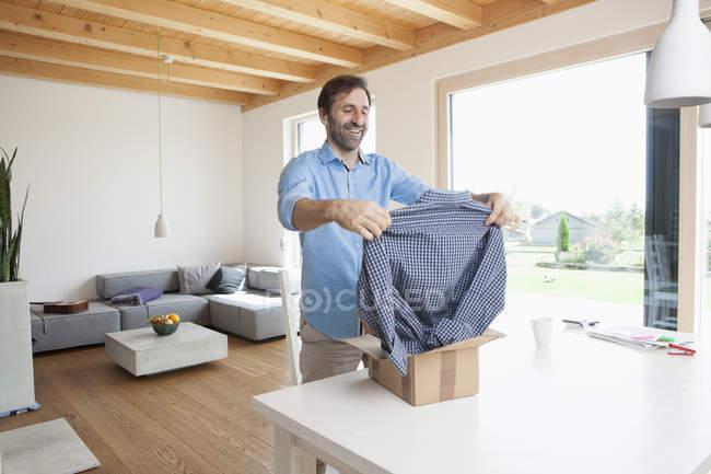 Hombre maduro en casa Desempaque nueva camiseta - foto de stock