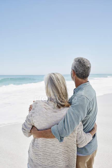 Взрослая пара обнимается на пляже — стоковое фото