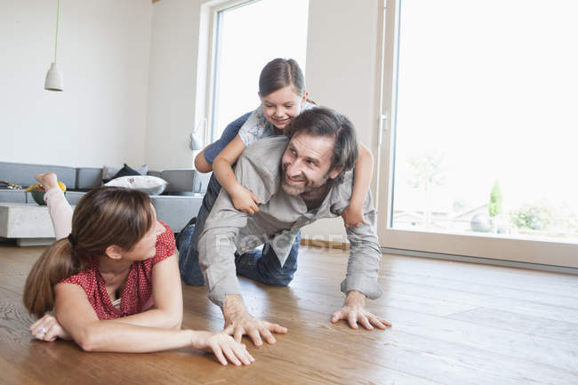 Щаслива родина лежав на підлозі, граючи з дочкою — стокове фото