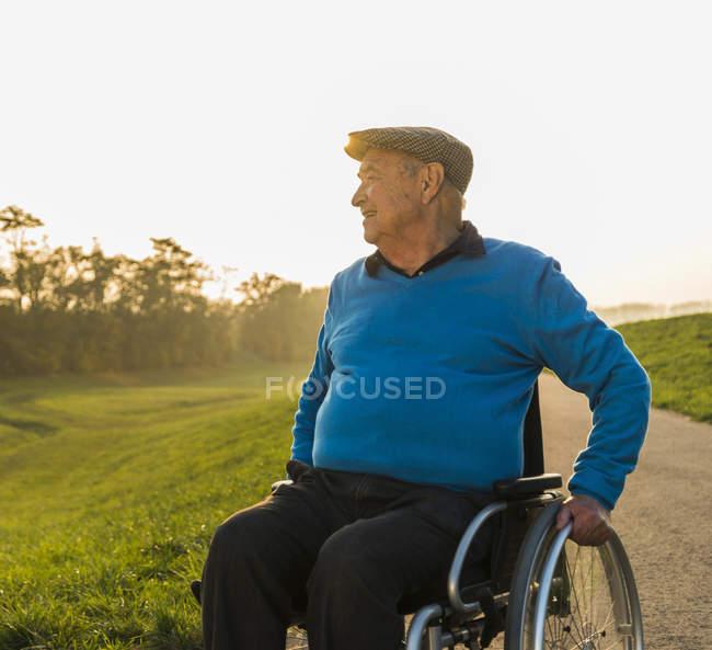 Старший мужчина в коляске в природе — стоковое фото