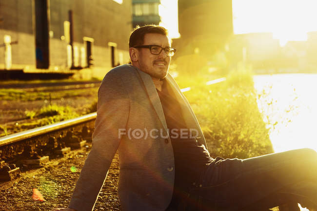 Man relaxing at city harbour in evening twilight — Stock Photo