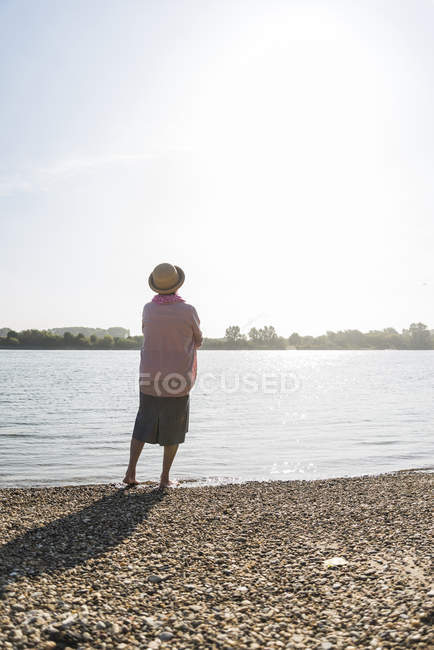 Back view of senior woman relaxing at riverside — Stock Photo
