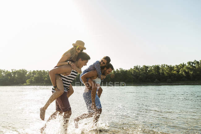 Two playful young couples having fun at river — Stock Photo