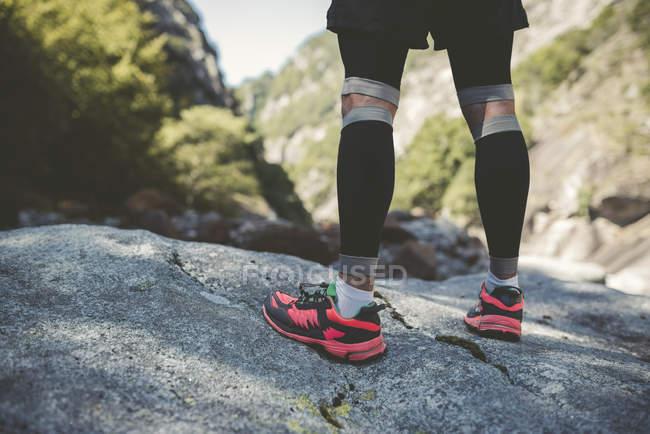 Ультра бегун в горах, стоящий на скале днем — стоковое фото