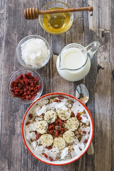 Schüssel Müsli mit Bananenscheiben, Chiasamen, Kokosraspeln und Goji-Beeren — Stockfoto
