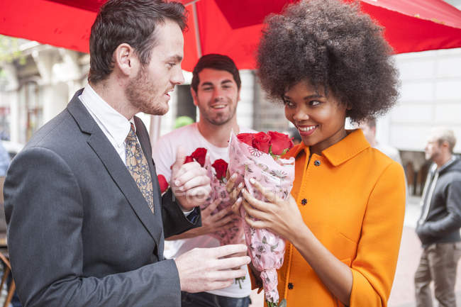 Молодой человек покупает красные розы для женщины — стоковое фото
