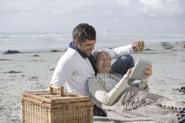 Paar mit digitalem Tablet beim Picknick am Strand — Stockfoto