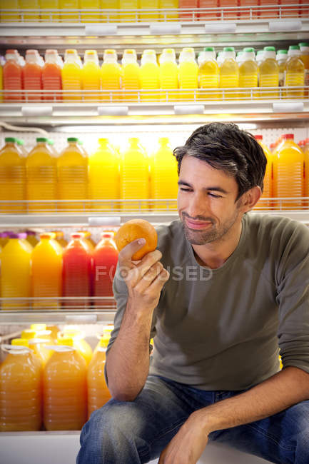 Portrait of smiling man sitting in front of fridge with rows of juice bottles in a supermarket holding an orange — Stock Photo