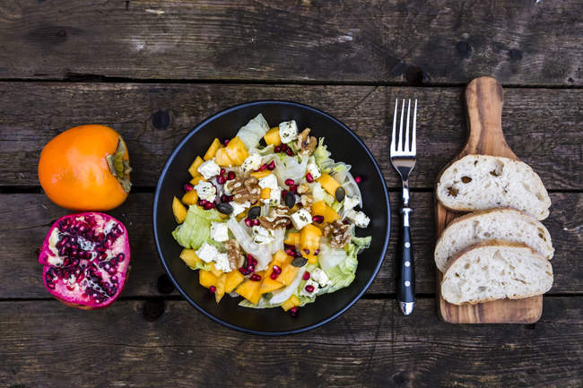Autumnal salad with kaki, feta cheese, iceberg lettuce, pumpkin seeds, pomegranate and walnuts — Stock Photo