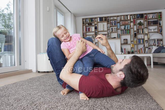 Uomo sdraiato sul pavimento a living room giocando con la sua piccola figlia — Foto stock
