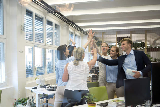 Successful business team high fiving in office — Stock Photo